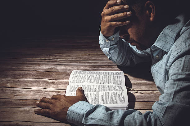 Worried man reading the Holy Bible stock photo