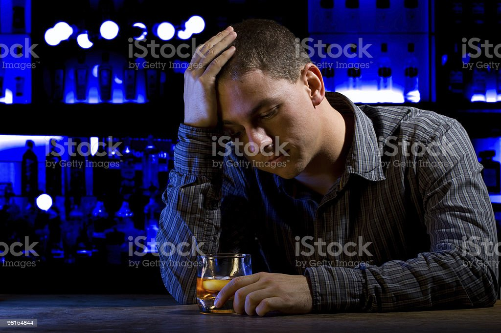 Worried man sitting at bar with whiskey glass. Dark scene. royalty-free stock photo