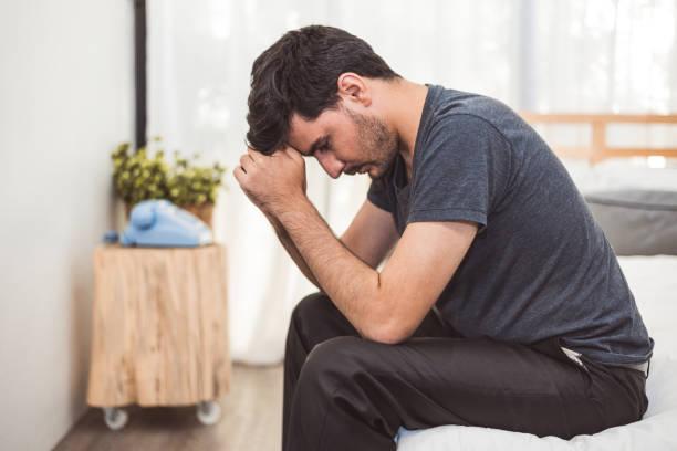 心配している人は、真剣な気分で寝室の額に手でベッドの上に座っています。mdd 概念と呼ばれる大うつ障害。男性の覚醒の孤独な症状。フィジカルヘルスケアと社会問題 - 憂鬱 ストックフォトと画像
