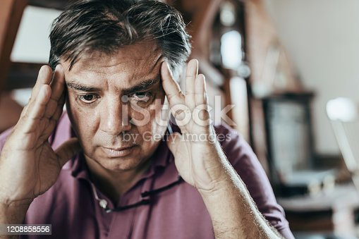 50s or 60s sad and worried man with grey hair sitting at home couch looking depressed and wasted in sadness face expression in depression and life problems