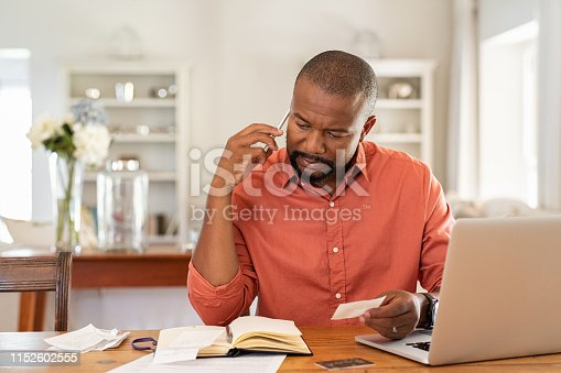Mature man paying bills with laptop while talking on phone. Thoughtful man at home in conversation over smartphone while checking receipts. Worried african man discussing expenses over phone with bank insurance.