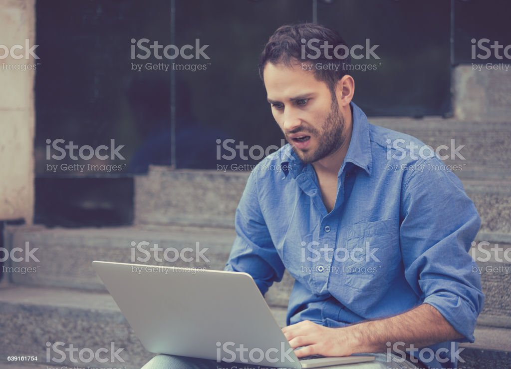 worried man working on laptop computer sitting outdoors stock photo