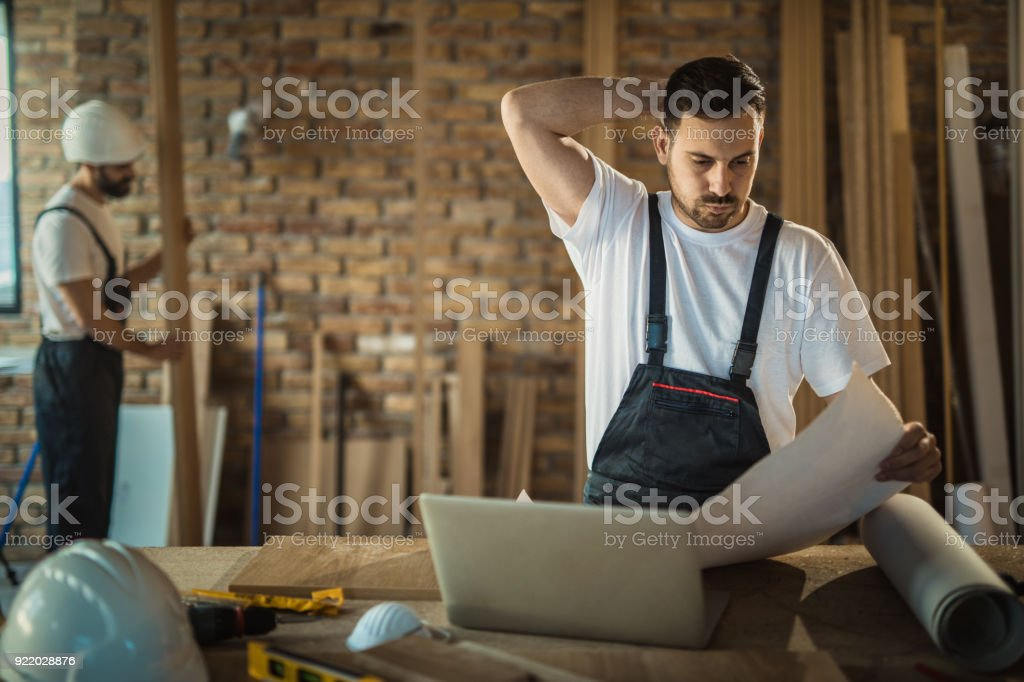 Worried manual worker having problems with blueprints at construction site. royalty-free stock photo