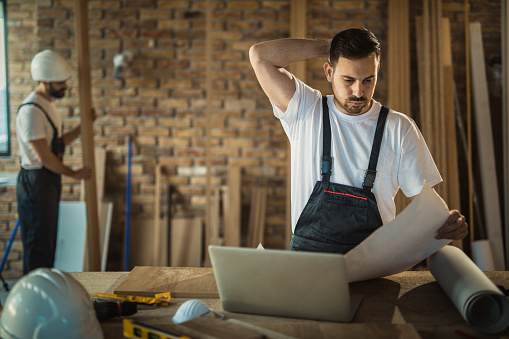 Worried Manual Worker Having Problems With Blueprints At Construction Site Stock Photo - Download Image Now