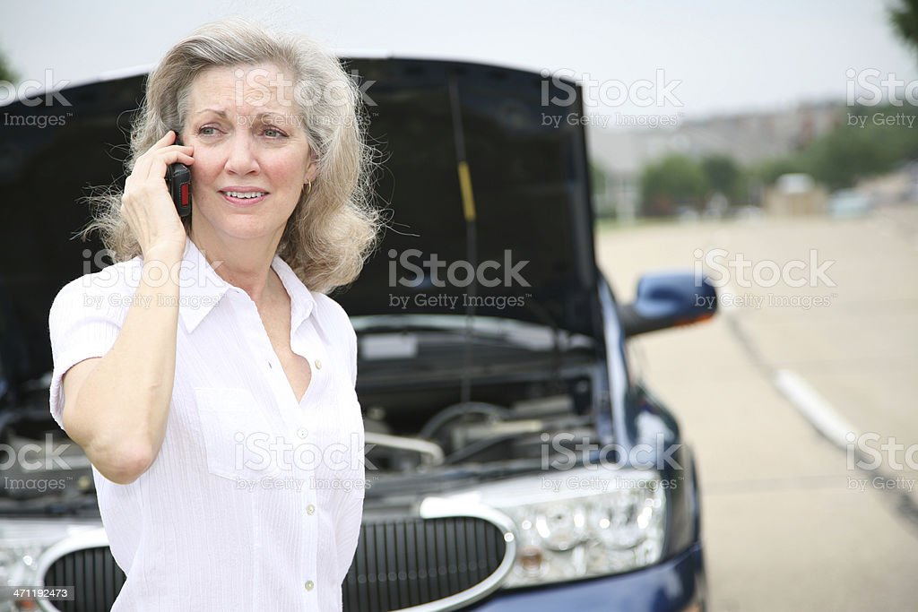 Worried Mature Adult Calling for Help With Her Car royalty-free stock photo