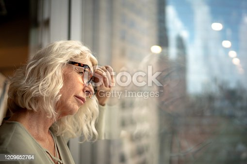 543048812 istock photo Worried mature businesswoman at window office 1209652764