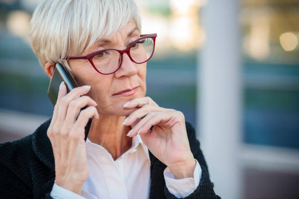 Worried mature businesswoman talking on the mobile phone, resting her arm on chin Worried mature businesswoman talking on the mobile phone, resting her arm on chin. Work anywhere concept. worried stock pictures, royalty-free photos & images