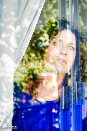 543048812 istock photo Worried mature Caucasian female looking cautiously out of a window 857103512