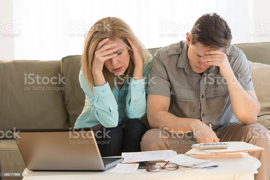 Worried mature couple calculating home finances on sofa stock photo