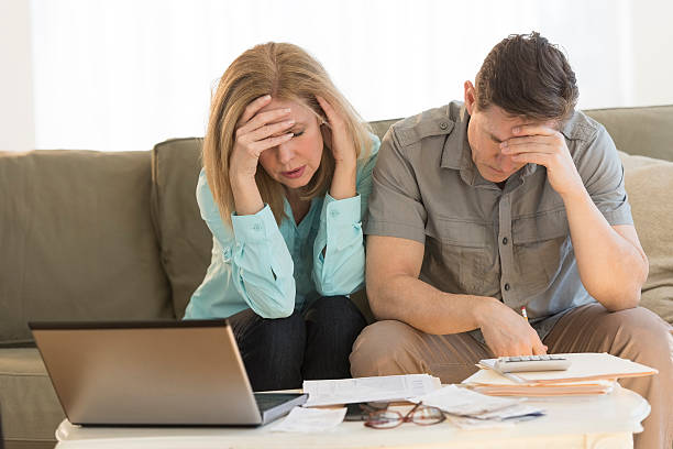 worried mature couple calculating home finances on sofa - bankruptcy stock pictures, royalty-free photos & images