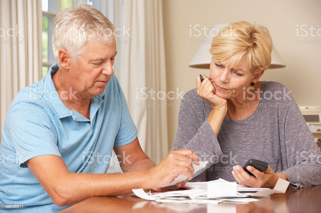 Worried Mature Couple Checking Finances And Going Through Bills stock photo