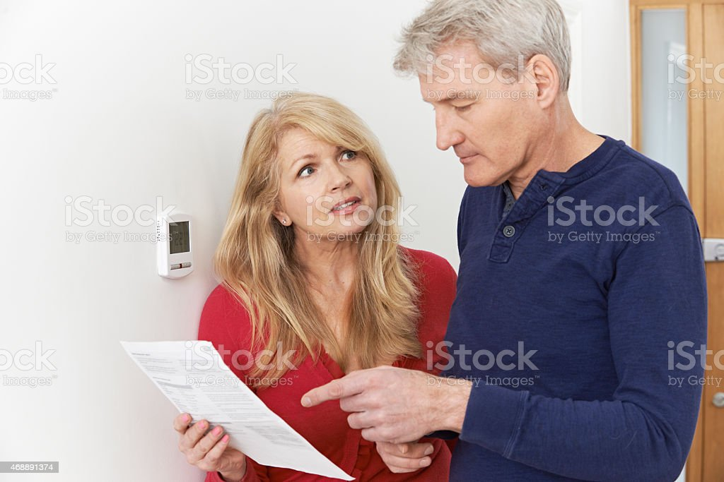 Worried Mature Couple With Bill Turning Down Central Heating stock photo