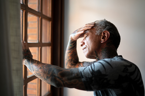 Worried mature man standing at home, close to a window, with hand in the head