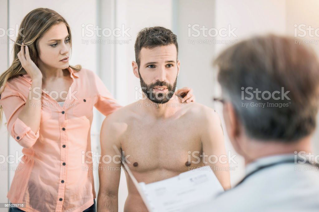 Worried mid adult man with his supportive wife waiting for medical results. stock photo