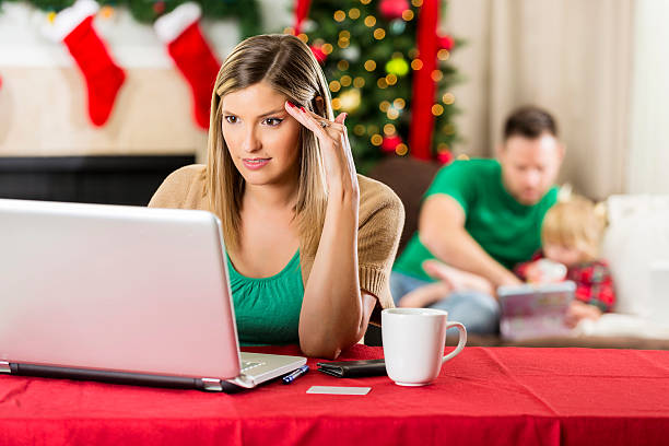 worried mom paying bills at christmastime - holiday and invoice family foto e immagini stock