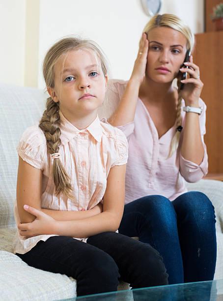Preocupado mãe telefone médico para filha com dores abdominais - foto de acervo