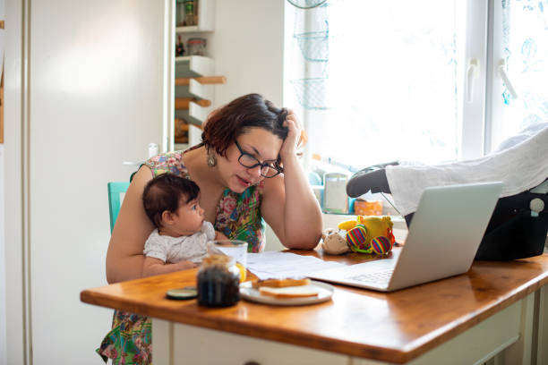 Worried mother paying bills online stock photo
