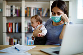 istock Worried mother with face protective mask working from home 1217382268