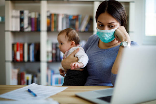 Worried mother with face protective mask working from home stock photo