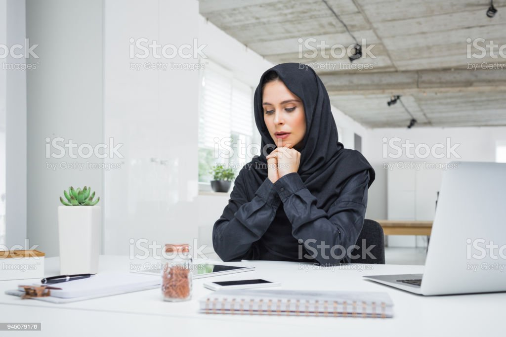 Worried muslim business woman working in office Worried business woman working on her laptop in the office. Muslim female in head scarf sitting at her desk. Adult Stock Photo