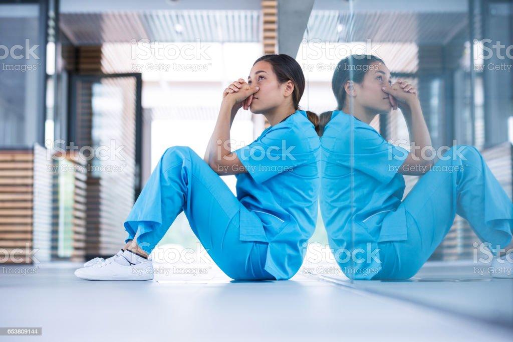 Worried nurse sitting on floor Worried nurse sitting in hospital corridor 30-34 Years Stock Photo