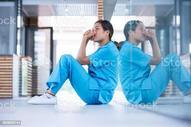 Worried Nurse Sitting On Floor Stock Photo - Download Image Now