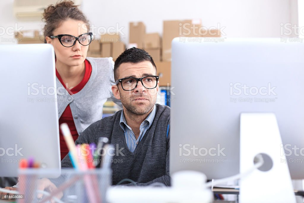 Worried office workers using computer in the office stock photo