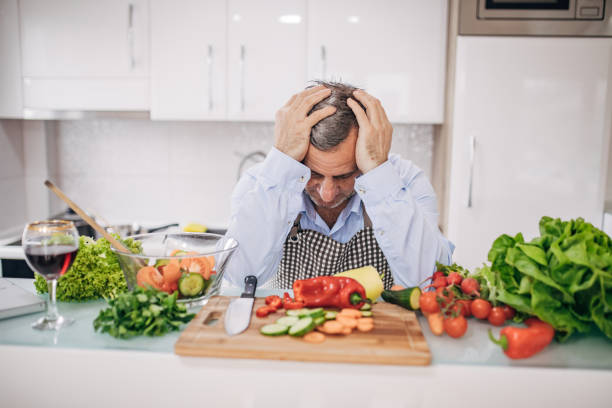 a worried old chef in the kitchen is taking a break - chef triste foto e immagini stock