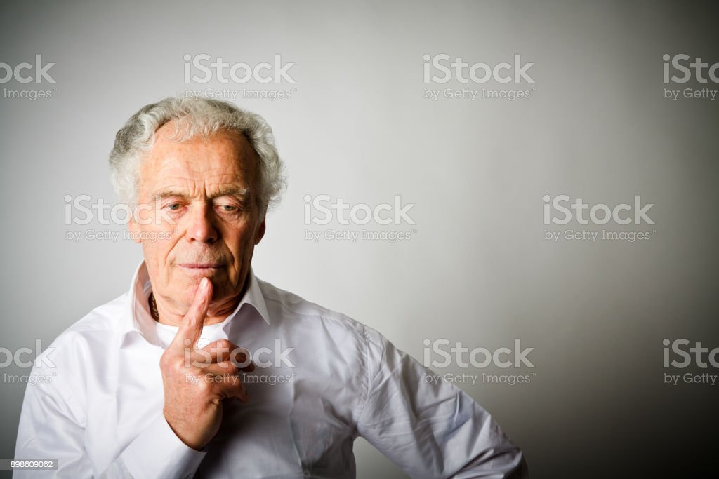 Worried. Old man in thoughts. Old man in white. stock photo