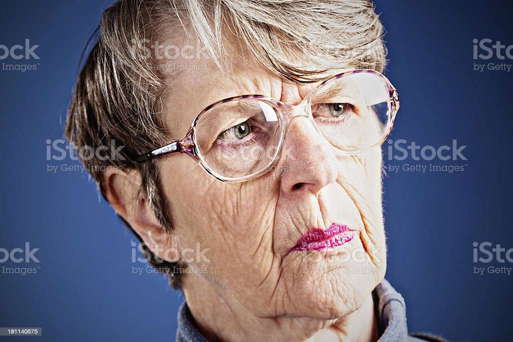 Worried old woman frowns in concern royalty-free stock photo