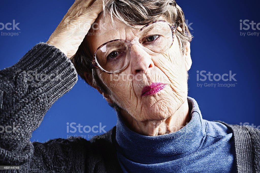 Worried old woman looks pained royalty-free stock photo