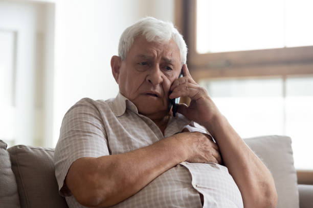 Worried older unhealthy man making emergency 911 call. Worried older unhealthy man sitting on couch, making emergency 911 call, having painful feelings in chest, heart attack disease symptoms. Unhappy frustrated elderly grandfather listening to bad news. bingo caller stock pictures, royalty-free photos & images