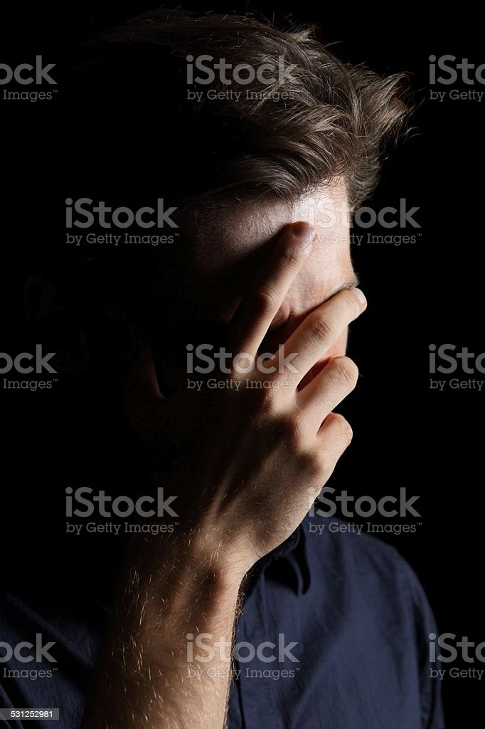 Worried or embarrassed man on black stock photo