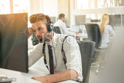 932342408istockphoto Worried or frustrated business man with headset working on computer in office 961477742