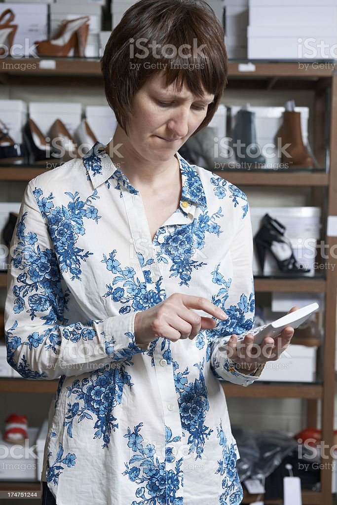 Worried Owner Of Shoe Store With Calculator royalty-free stock photo