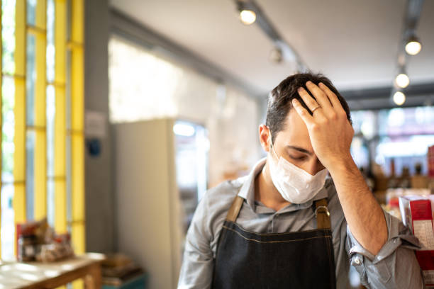 Worried owner with face mask at his small business stock photo