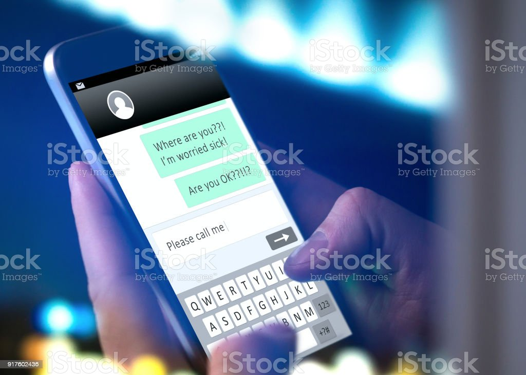 Worried parent writing text message to child that doesn't come home or answer or man typing sms to lost friend. Hand holding mobile phone late at night. stock photo