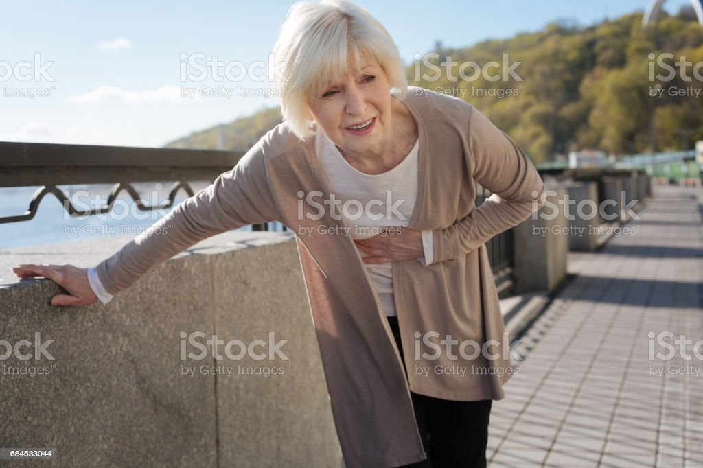Worried pensioner having terrible pain in the street stock photo