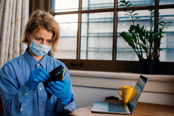 worried person with virus protection mask and gloves holding wallet at home by the window - carlos david stock pictures, royalty-free photos & images