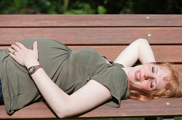 besorgt schwangere frau ruhen auf einer bank - angst vor der geburt stock-fotos und bilder
