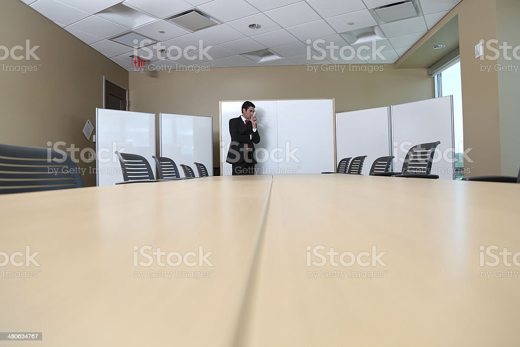 worried presenter thinks about his presentation in boardroom stock photo