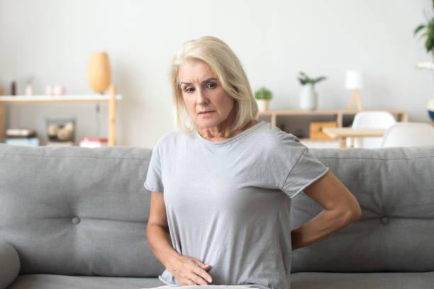 worried sad older woman touching back feeling back pain - ernia foto e immagini stock
