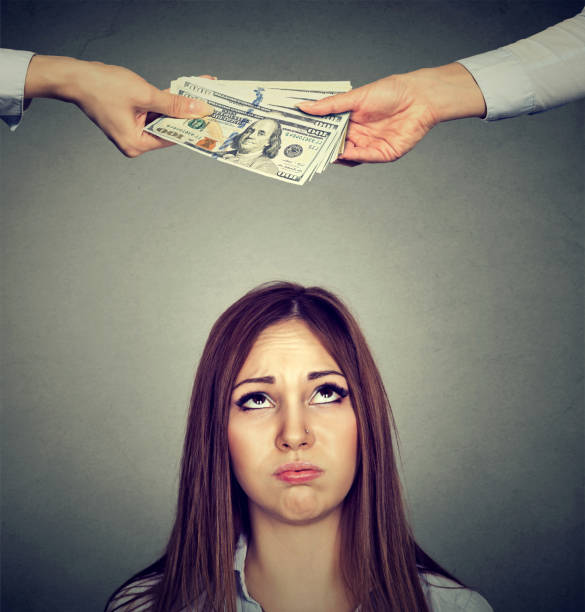 worried sad woman looking up at two hands exchanging money - moldova stock pictures, royalty-free photos & images