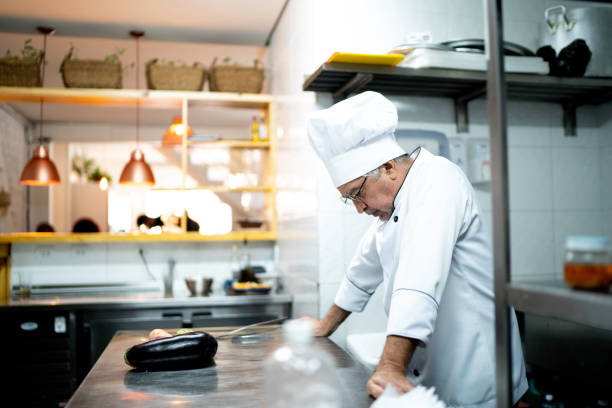 a worried senior chef in the kitchen counter - small business owner stock pictures, royalty-free photos & images