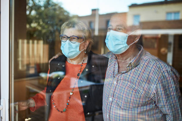 Worried senior couple looking through window at home in quarantine stock photo