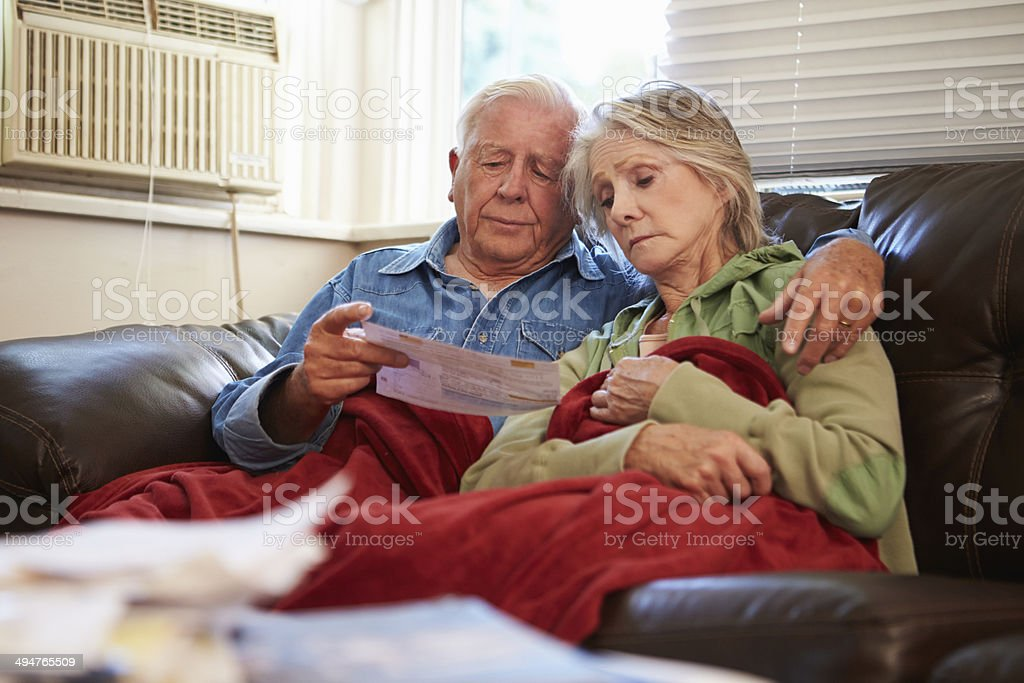 Worried Senior Couple Sitting On Sofa Looking At Bills stock photo