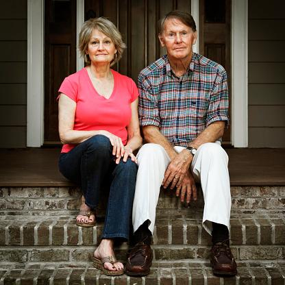istock Worried Senior Couple Sitting Outside House On Step 668312328