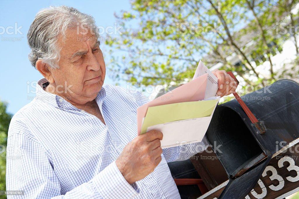 Worried Senior Hispanic Man Checking Mailbox royalty-free stock photo