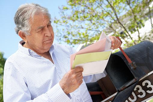 Worried Senior Hispanic Man Checking Mailbox