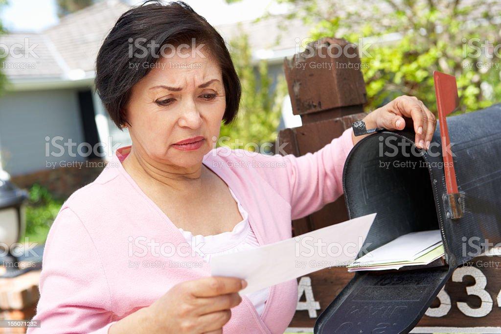 Worried Senior Hispanic Woman Checking Mailbox royalty-free stock photo